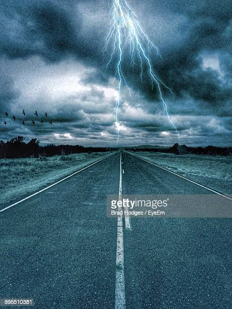 Country Road Against Forked Lightning In Cloudy Sky