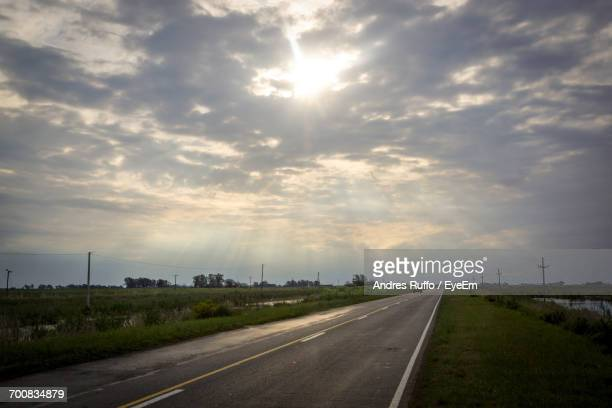 country road amidst field against cloudy sky - andres ruffo stock pictures, royalty-free photos & images