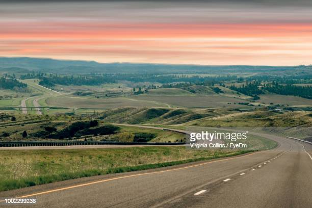 country road amidst field against sky - billings montana stock pictures, royalty-free photos & images