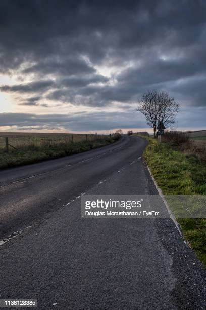 country road amidst field against sky - gillingham stock pictures, royalty-free photos & images