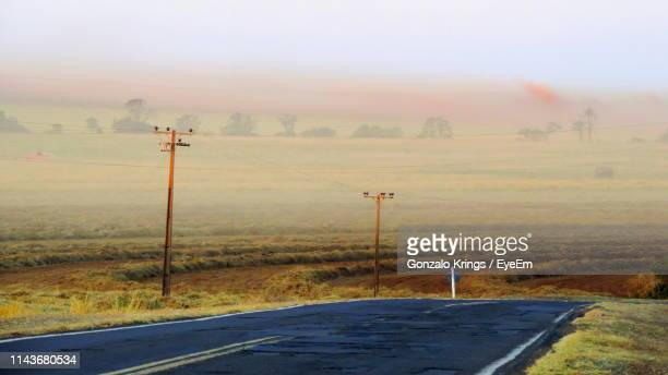 country road amidst field against sky - krings stock pictures, royalty-free photos & images