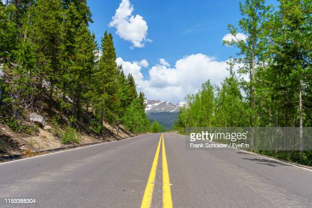 country road amidst trees against sky - frank schrader stock pictures, royalty-free photos & images