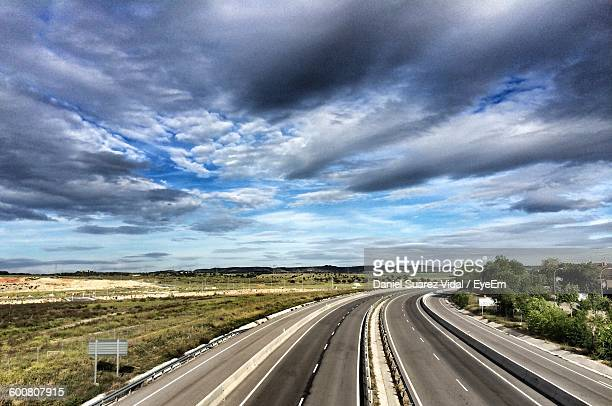 country road by field against cloudy sky - suarez stock pictures, royalty-free photos & images