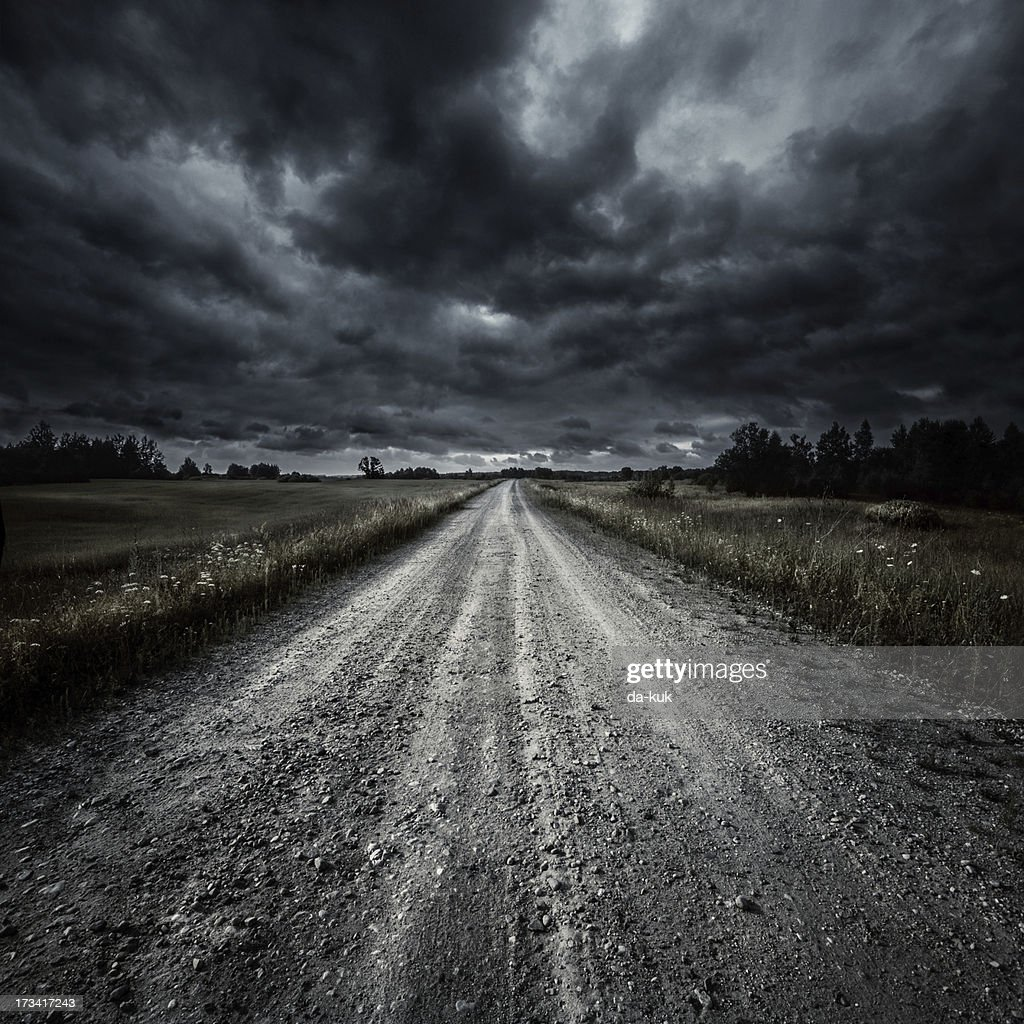 Country road in a field at storm : Stock Photo
