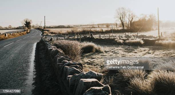 country road in a frosty rural scene - falls road stock pictures, royalty-free photos & images