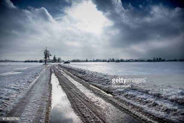 country road in winter - sleet stock photos and pictures