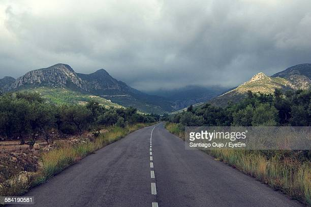Country Road Leading Towards Mountain Against Cloudy Sky
