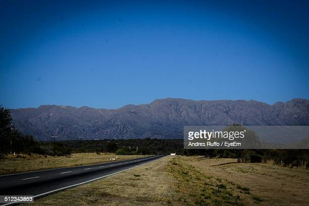 country road leading towards mountains against clear blue sky - andres ruffo stock-fotos und bilder