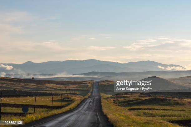 country road leading towards mountains against sky - sivas stock pictures, royalty-free photos & images