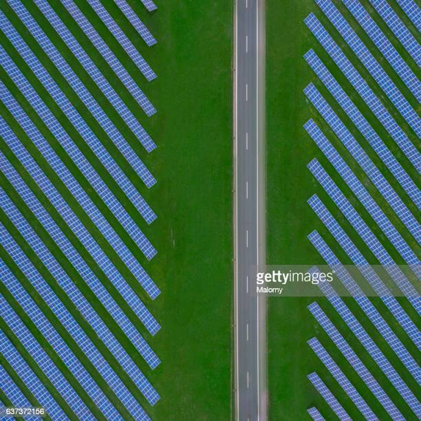 Country road near solar farm or solar power plant, top view, view from above, aerial view