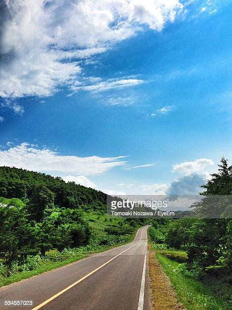 Country Road On Green Mountain Against Blue Sky