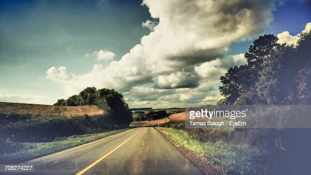 Country Road Passing Through Landscape Against Cloudy Sky