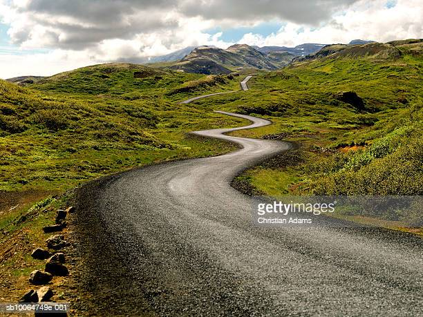 country road passing through mountains - winding road stock pictures, royalty-free photos & images