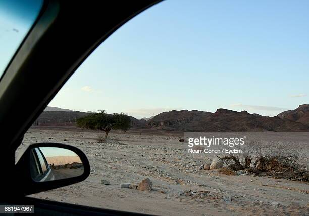 country road seen through car window - noam cohen stock pictures, royalty-free photos & images
