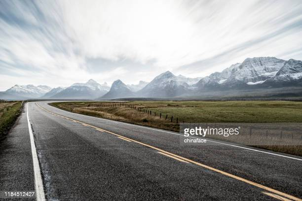 country road towards snow mountains against sky, canada - alberta stock pictures, royalty-free photos & images