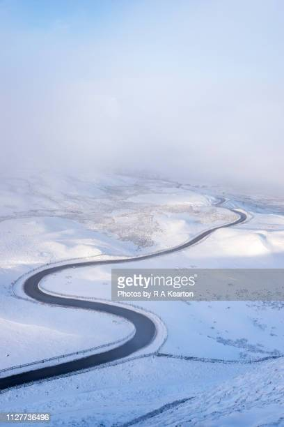 country road winding through a snowy landscape - extreme weather stock photos and pictures