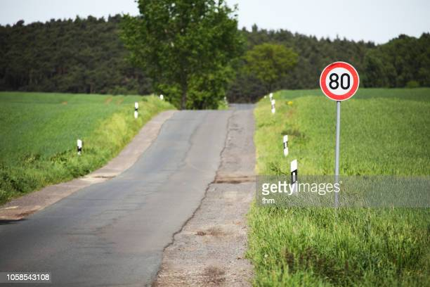 country road with a speed limit sign - speed limit sign stock photos and pictures