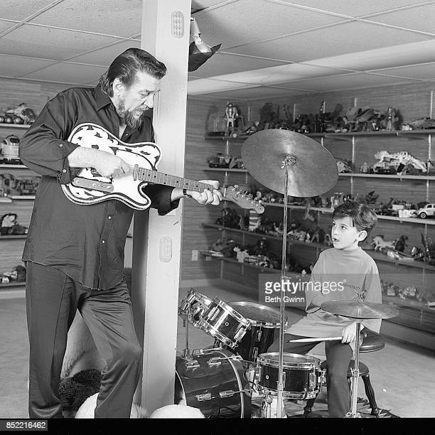 Country singer and songwriter Waylon Jennings and son Shooter Jennings jam together at home on December 9 1987 in Nashville Tennessee