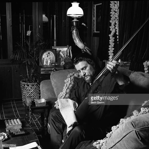 Country singer and songwriter Waylon Jennings cleans a gun while in his living room on December 9 1987 in Nashville Tennessee