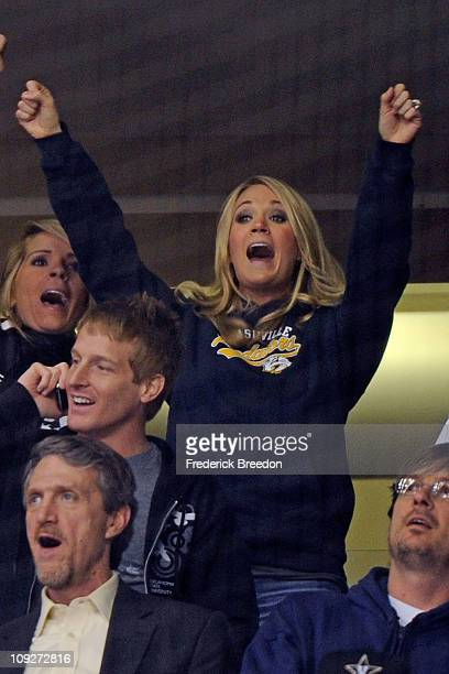 Country singer Carrie Underwood reacts to her husband Mike Fisher of the Nashville Predators scoring a goal against the Vancouver Canucks on February...