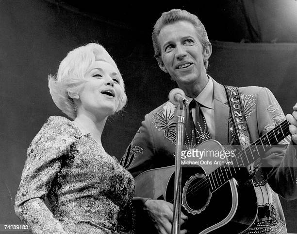 Country singer Dolly Parton and her collaborator Porter Wagoner perform onstage in circa 1967 Mr Wagoner is wearing a Nudie Suit designed by Nudie...