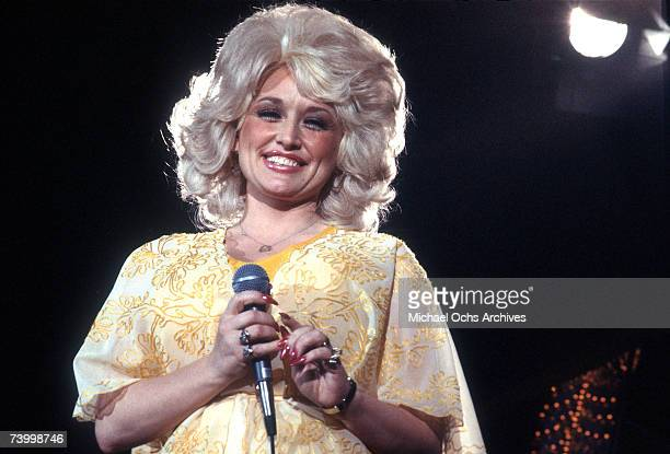 Country singer Dolly Parton performs onstage wearing a yellow dress, circa 1975, Los Angeles, California.
