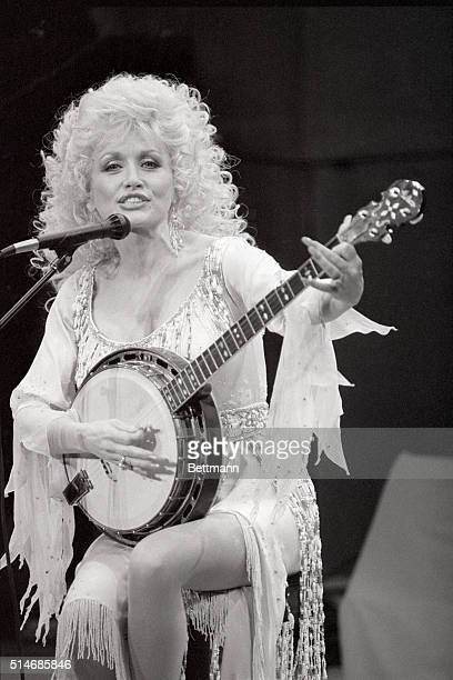 Country singer Dolly Parton sings and plays the banjo at a concert in Lincoln Center.
