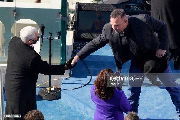 Country singer Garth Brooks shakes hands with former Vice President Mike Pence during the 59th presidential inauguration on the West Front of the...