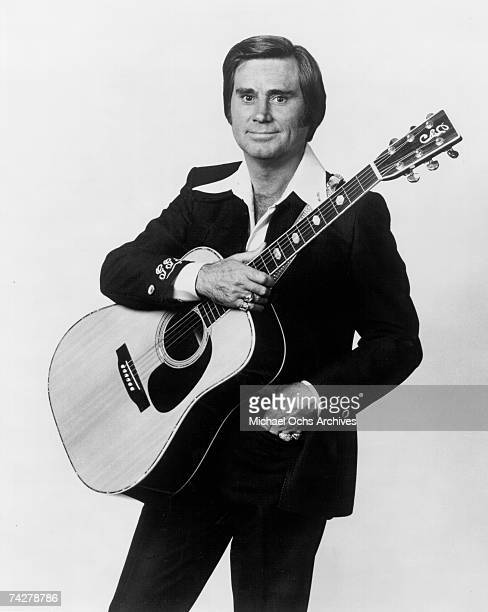 Country singer George Jones poses for a portrait holding an acoustic guitar in circa 1976
