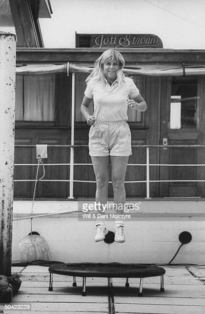 Country singer Jett Williams illegitimate daughter of late singer Hank Williams Sr in shorts tshirt jumping on a small round exercise trampoline on...
