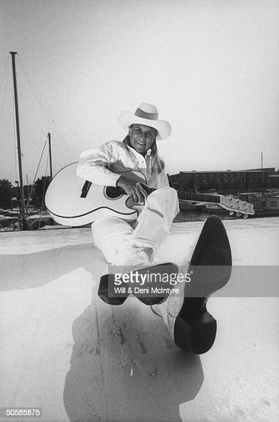 Country singer Jett Williams illegitimate daughter of late singer Hank Williams Sr wearing white cowboy hat shirt jeans as she poses w white guitar...