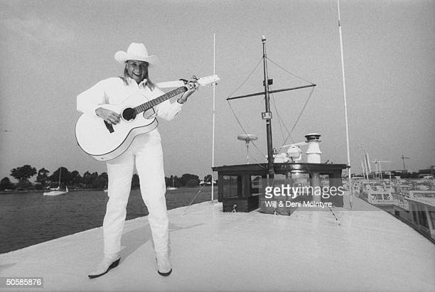 Country singer Jett Williams illegitimate daughter of late singer Hank Williams Sr wearing white cowboy hat shirt jeans as she plays a white guitar...