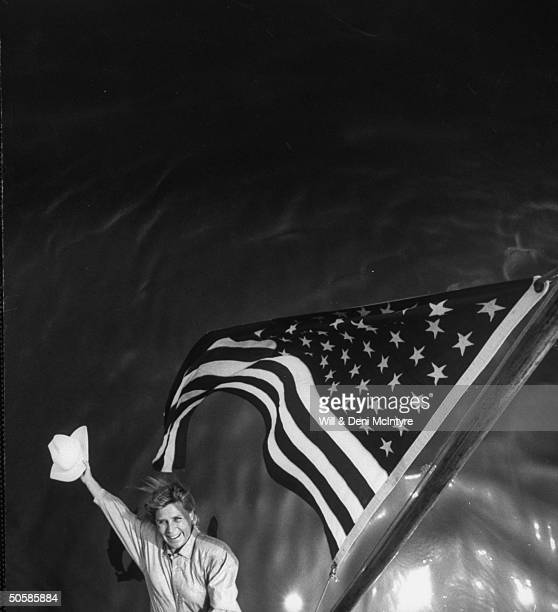 Country singer Jett Williams illegitimate daughter of late singer Hank Williams Sr waving white cowboy hat as she stands next to gloriously waving...