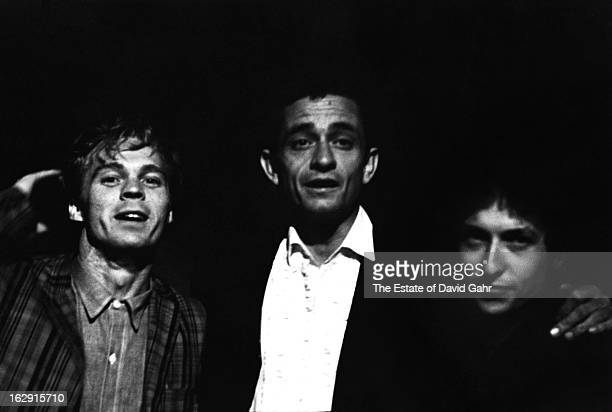Country singer Johnny Cash backstage with bluegrass mandolinist Frank Wakefield and singer songwriter Bob Dylan at the Newport Folk Festival in July...