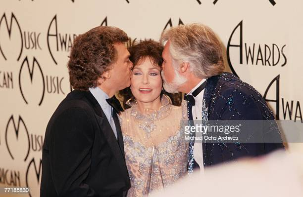 Country singer Loretta Lynn poses for a portrait as Conway Twitty and Kenny Rogers each kiss a cheek at the American Music Awards which were held at...