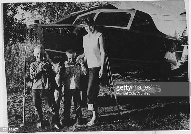 Country singer Loretta Lynn poses for a portrait with 3 little boys in circa 1950 in Butcher Holler Kentucky