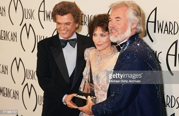 Country singer Loretta Lynn poses for a portrait with Conway Twitty and Kenny Rogers at the American Music Awards which were held at the Santa Monica...