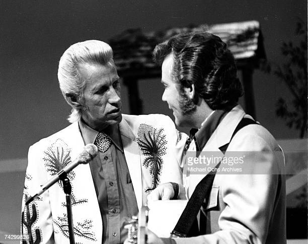 Country singer Porter Wagoner interacts with a man holding an acoustic guitar in circa 1970 Mr Wagoner is wearing a Nudie Suit designed by Nudie Cohn...