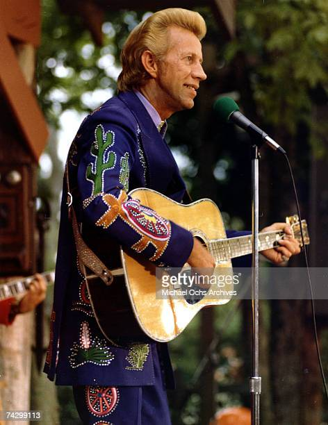 Country singer Porter Wagoner performs onstage with an acoustic guitar in circa 1973 Mr Wagoner is wearing a Nudie Suit designed by Nudie Cohn of...
