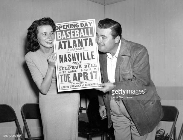 Country singer songwriter June Carter Cash holds an Atlanta Crackers versus Nashville Vols poster with a WMAK DJ in 1951 in Nashville, Tennessee.