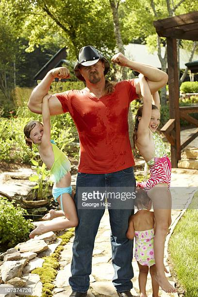 Country singer Trace Adkins with daughters Hadley Mackenzie and Trinity at a portrait session for People Country on July 15 2010 in Brentwood...