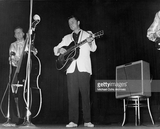 """Country singer/songwriter Johnny Cash performs onstage with his backing band """"The Tennessee Two"""" which consisted of bassist Marshall Grant and..."""