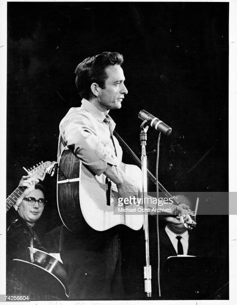 Country singer/songwriter Johnny Cash plays acoustic guitar as he performs onstage in circa 1965