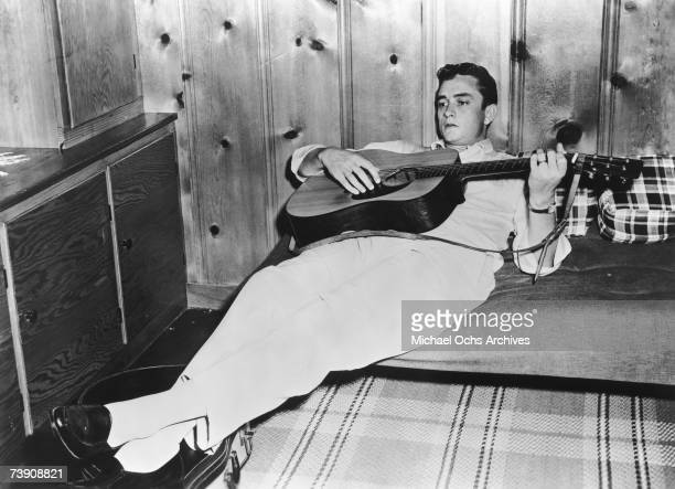 Country singer/songwriter Johnny Cash plays acoustic guitar as he reclines on a bed in 1958 in Memphis Tennessee