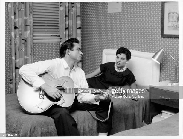 Country singer/songwriter Johnny Cash sits on a bed playing acoustic guitar as his first wife Vivian Liberto looks on in circa 1957.