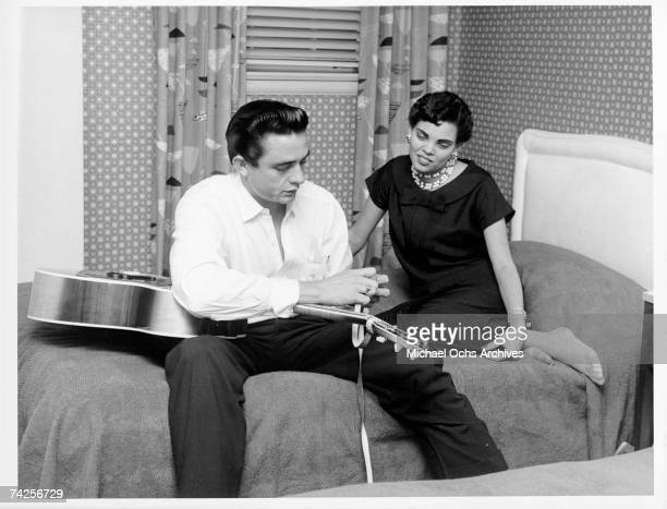 Country singer/songwriter Johnny Cash sits on a bed tying his guitar strap as his first wife Vivian Liberto looks on in circa 1957
