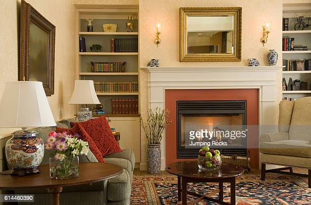 Country style sitting room with sofa and armchairs and fireplace New England USA