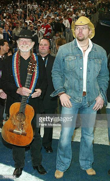 Country western artists Willie Nelson and Toby Keith chat before the pre-game show prior to the start of Super Bowl XXXVIII between the New England...