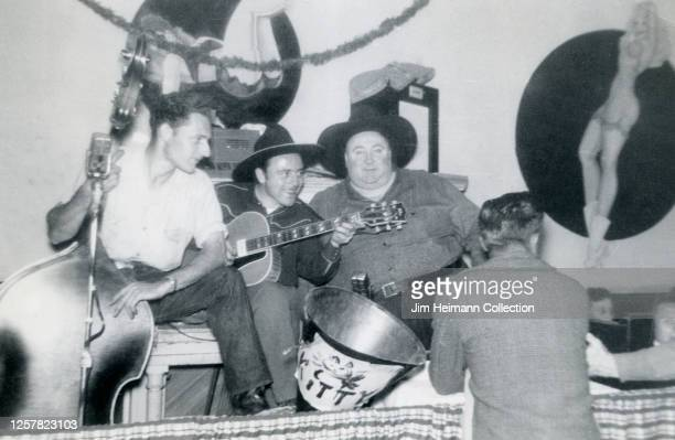 Country western band consisting of three middle-aged men sit on a stage with their instruments getting ready to perform, circa 1950.