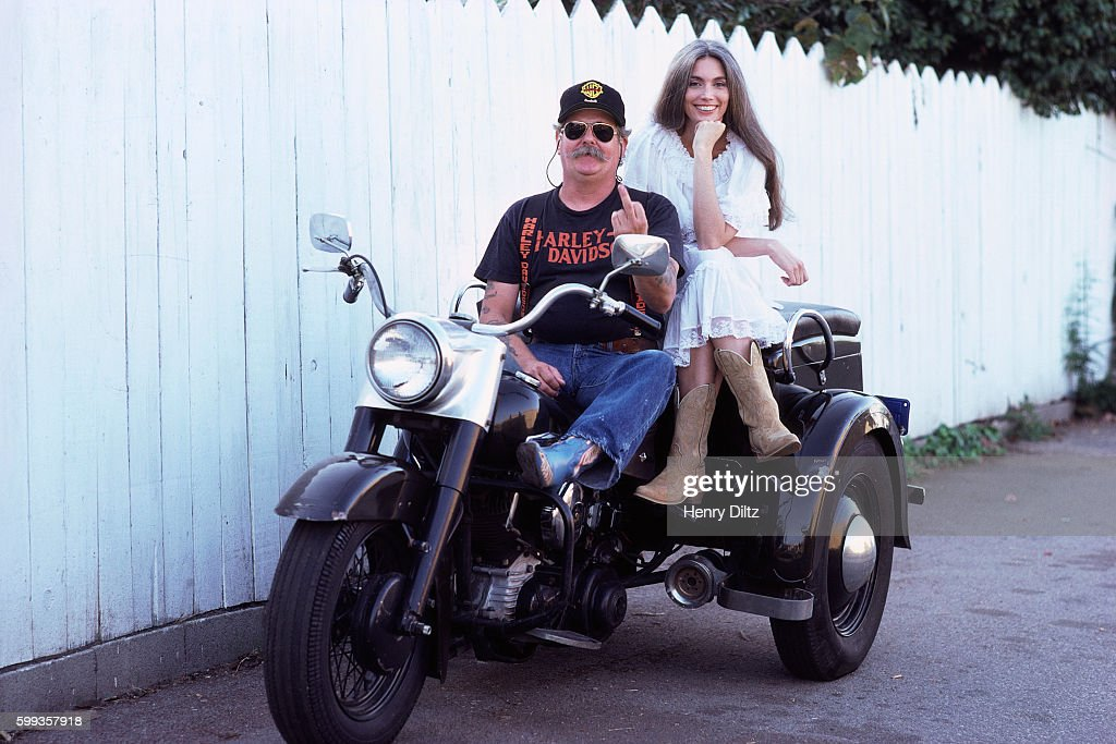 Country-folk singer Emmylou Harris sits on the back of a three-wheeled motorcycle with manager Phil Kaufman, who is flipping the bird.